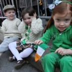 Jack O'Rourke, 4, left, and his twin sister Claire O'Rourke share a laugh as Mia Hayes, 4, right, holds an Irish flag as they watch the St. Patrick's Day Parade make it's way up New York's Fifth Avenue. 