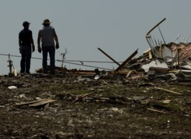Locals watch as a tractor pulls down what's left of one of their homes in Joplin, Missouri, late last month.