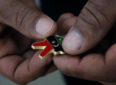 A Libyan man holds a souvenir of the Libyan revolution in the colors of the pre-Gadhafi flag.