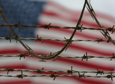 A flag waves behind the barbed and razor-wire at the detention compound on Guantanamo Bay US Naval Base in Cuba