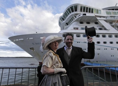 Passengers from the cruise pose in front of the vessel