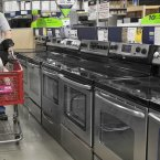 Tom Klitzke walks his pugs Max and Bear past home appliances at a Lowe's store in Omaha. (AP Photo/Nati Harnik)