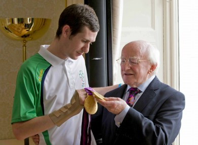 Double gold medal winner Michael McKillop shows off his prizes to President Michael D. Higgins at the Aras yesterday.