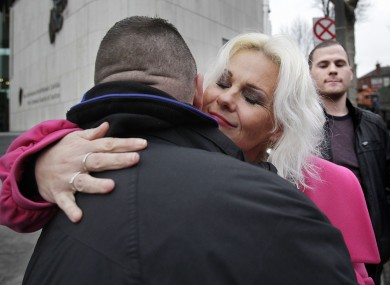 Fiona Doyle leaving the Central Criminal Court in Dublin today embraces her husband Jim (left) and with her son Paddy (right)
