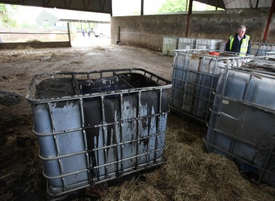 A customs officer looks at containers of sludge at a fuel laundering plant unearthed in Knightstown, Co Meath, following a raid by Customs and Garda officers in 2011.