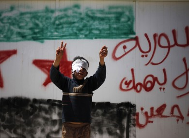 Syrian refugee Bashar al-Zalfi, 10, waves the victory sign while posing in front of a wall with the colors of the revolutionary flag, and Arabic reading,