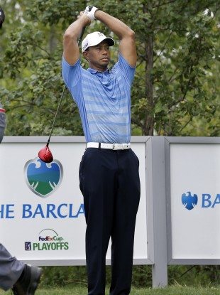 Tiger Woods stretches his stiff back before teeing off at The Barclays golf championship.