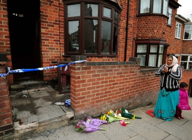 A local resident says a prayer outside the scene of the fatal house fire in Wood Hill, Leicester.