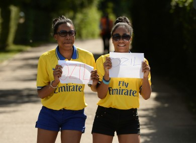 Arsenal fans Kimberley (left) and Yasmine Blackman show their support for Mesut Ozil outside Arsenal FC's London Colney training ground today.